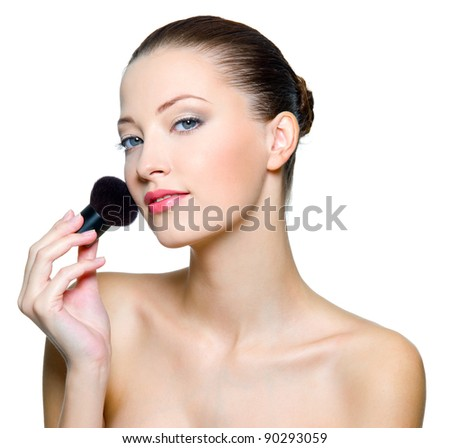 Beautiful woman doing make-up on face with cosmetic brush. Fashion model posing on white background