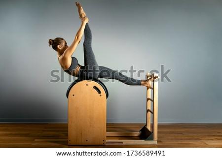 Beautiful woman doing pilates exercise, training on barrels. Barrel reformer, correct posture, healthy locomotor system.