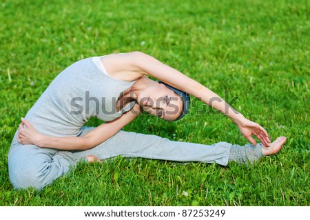 Beautiful woman doing stretching exercise on green grass at park. Yoga - stock photo