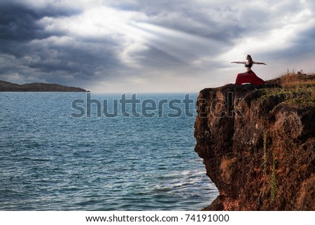Beautiful woman doing virabhadrasana warrior yoga pose on the cliff near the ocean with dramatic sky at background in India