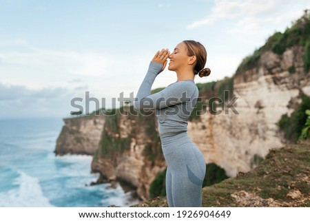 Beautiful woman doing yoga on a cliff, behind an amazing view in the ocean Bali Indonesia 商業照片 ©