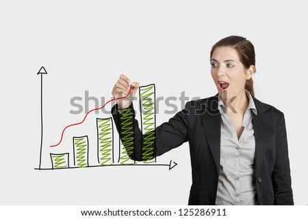 Beautiful woman drawing a business chart on a glass board with a marker