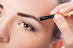Beautiful woman drawing a shape of eyebrows using cosmetic brush. Make up artist applying make up to a model