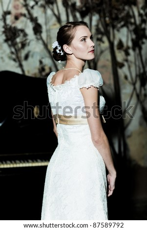 beautiful woman dressed as a bride standing next to piano