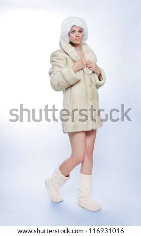 Beautiful woman dressed in fur coat walking on blue background.