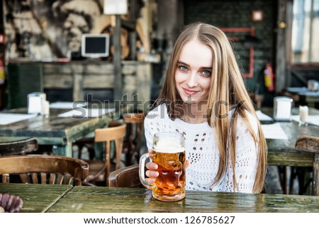 Beautiful woman drinking beer at the cafe - stock photo