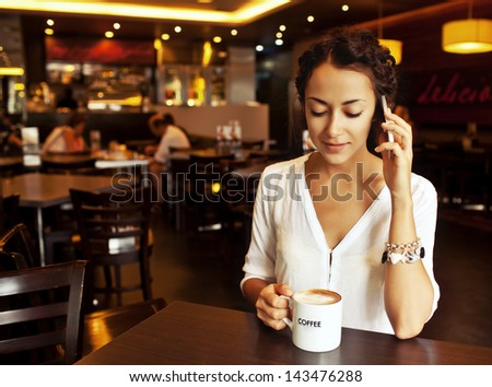 Beautiful Woman Drinking Coffee and talking on cellphone - stock photo