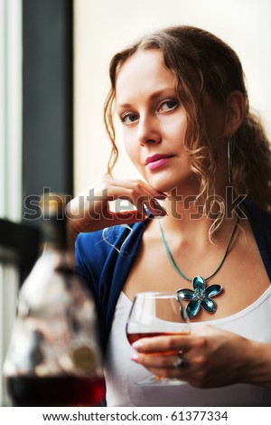 Beautiful woman drinking cognac.