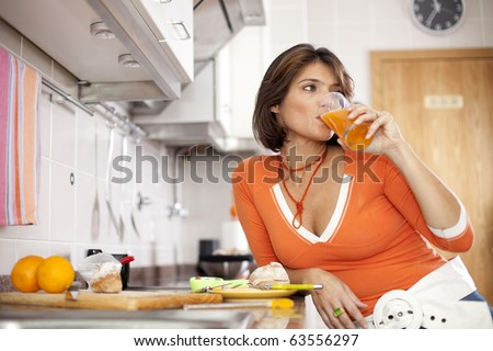beautiful woman drinking her orange juice and looking natural at her kitchen (selective focus with shallow DOF)
