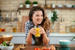 Beautiful woman drinking orange healty orange juice in the kitchen
