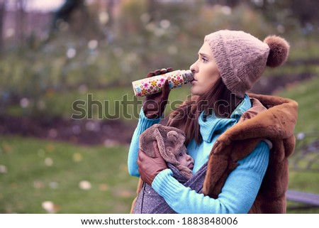 beautiful woman drinking tea or water from a thermos in winter with a warm hat and sweater carrying her son. style of life. motherhood concept stock photo