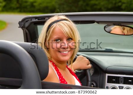 Beautiful woman driver  in open top convertible. - stock photo