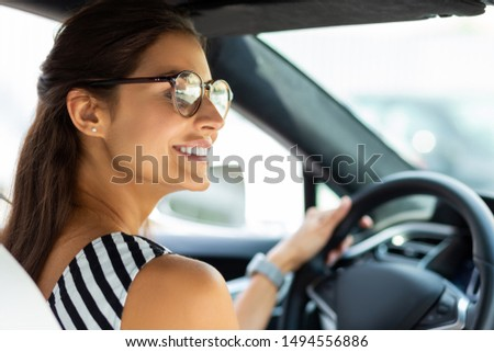 Beautiful woman driving. Beautiful smiling woman driving her car and looking into right side mirror