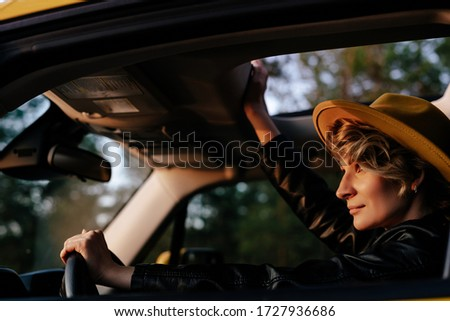Beautiful Woman Driving Car Side View Portrait. Gorgeous Stylish Blonde Female Sitting at Wheel Watching Sunset Road. Carefree Caucasian Girl Enjoying Comfortable Auto Journey with Open Sunroof Foto stock ©
