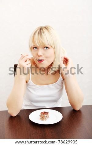 Beautiful woman eating cake. In home.