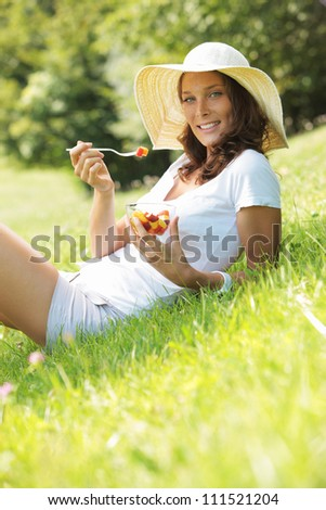 Beautiful woman eating fruit salad on a lawn