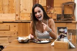 Beautiful woman eating traditional Balkan dish in restaurant