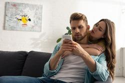 Beautiful woman embracing addicted boyfriend with smartphone on sofa