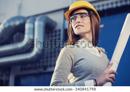 beautiful woman engineer is standing in front of an industrial pipes background
