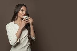 Beautiful woman enjoying coffee on brown background