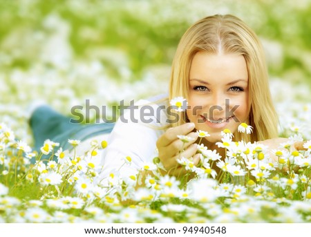 Beautiful woman enjoying daisy field, nice female lying down in meadow of flowers, pretty girl relaxing outdoor, having fun, holding plant, happy young lady and spring green nature, harmony concept