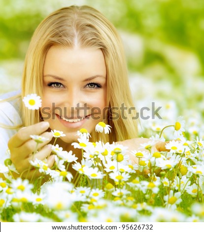 Beautiful woman enjoying daisy field, nice female lying down in the meadow of flowers, pretty girl relaxing outdoor, having fun,holding plant, happy young lady and spring green nature, harmony concept