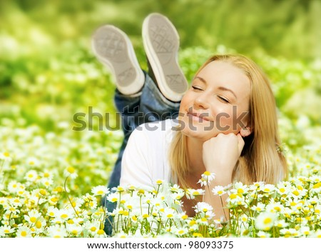 Beautiful woman enjoying daisy field, nice female lying down in the meadow of flowers, pretty girl relaxing outdoor, having fun, happy young lady and spring green nature, harmony and freedom concept