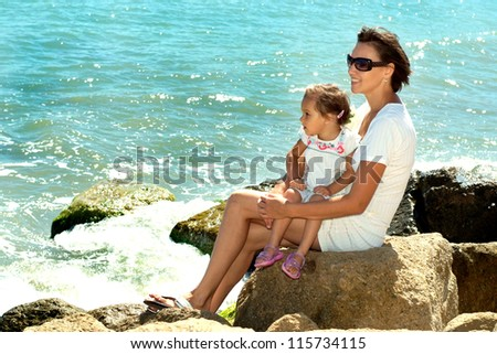 Beautiful woman enjoying the sea breeze with her daughter