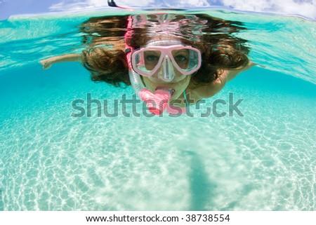 beautiful woman enjoys snorkeling in tropic waters