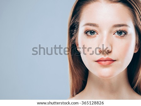 Beautiful woman face close up portrait young studio on gray background