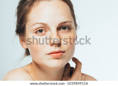 Beautiful woman face close up with freckles isolated, cleam skin - Shutterstock ID 1039849156