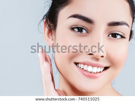 Beautiful woman face closeup portrait hands on skin #740511025