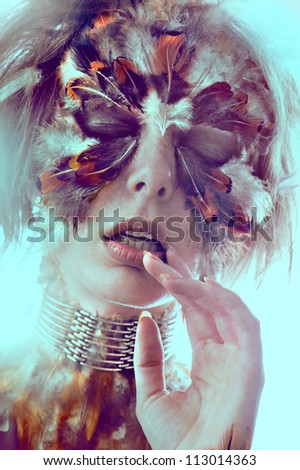 Beautiful woman face dramatic creative face-art of the feathers of wild birds framing and enhancing her eyes