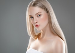 Beautiful Woman Face Portrait Beauty Skin Care Concept with long blonde hair. Fashion Beauty Model with beautiful hairstyle over gray background