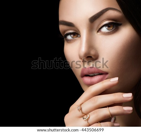 Beautiful woman face portrait isolated on black background. Sexy lips with fashion natural beige matte lipstick makeup, beige nails, trendy midi rings on her fingers. Closeup