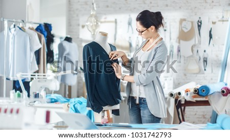Beautiful Woman fashion, designer,  Working with Tailoring Mannequin, Adjusting Blouse. Her Studio is Bright and Sunny, Mannequins Standing around, Clothes Hanging, Colorful Fabrics Lying on the Table Foto stock ©