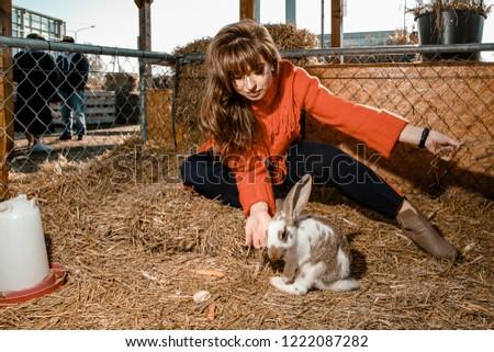 beautiful woman feeds farm of rabbits. #1222087282