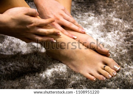 Beautiful woman feet and hands touching the soft skin, pampering foot and hand care, luxury french manicure and pedicure on beautiful toned nails, abstract grey background, dramatic light contrast #1108951220