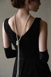 Beautiful woman figure in profile in a black dress and pearls in the style of 20-30 years of the XX century