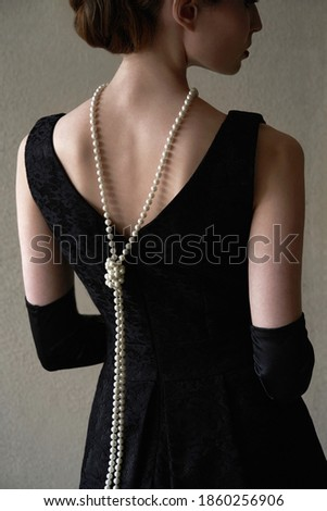Beautiful woman figure in profile in a black dress and pearls in the style of 20-30 years of the XX century     Stockfoto ©