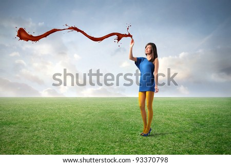 Beautiful woman filling the air with red paint on a green meadow
