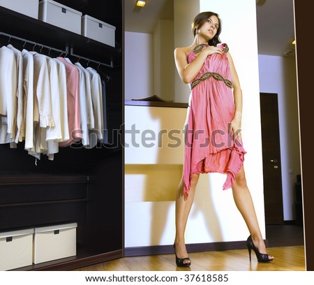 beautiful woman fits on a pink dress in the shopping mall