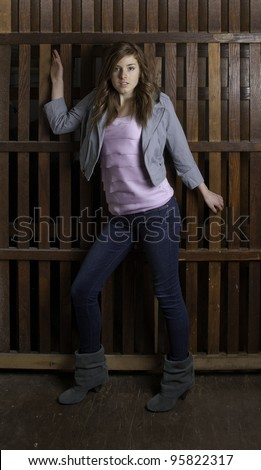 Beautiful woman fleeing in front of wooden bars of freight elevator.