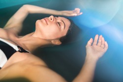 Beautiful woman floating in tank filled with dense salt water used in meditation, therapy, and alternative medicine.