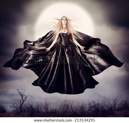 Beautiful woman - flying halloween witch in midnight outdoor about full moon with black developing cloak