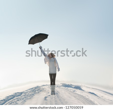 Stock Photo beautiful woman flying with umbrella on road in winter