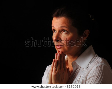 Beautiful woman gazing up to heaven with hands folded in prayer