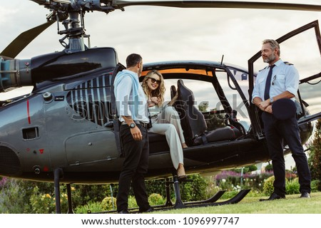 Beautiful woman getting down the helicopter with the help from her boyfriend. Couple disembarking their helicopter with pilot standing by.