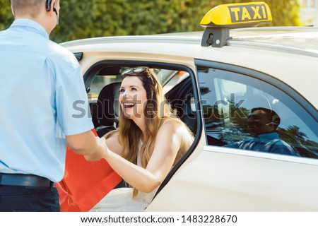 Beautiful woman getting out of taxi and the driver helping her Foto stock ©