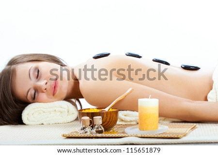 beautiful woman getting treatment with spa stones in spa salon